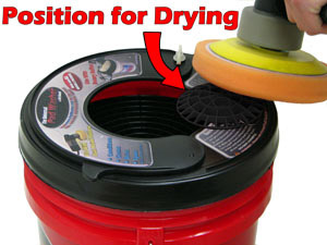 Dry pads by spinning them against the Grid Extension positioned on the outside of the bucket.