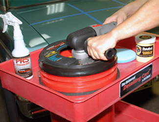Washing a pad in the Grit Guard Universal Pad Wash on the Universal Detailing Cart