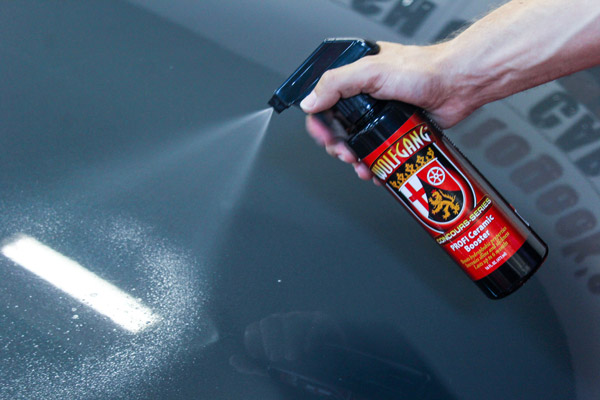this image shows someone spraying Wolfgang PROFI Ceramic Booster directly onto the paint surface of a car