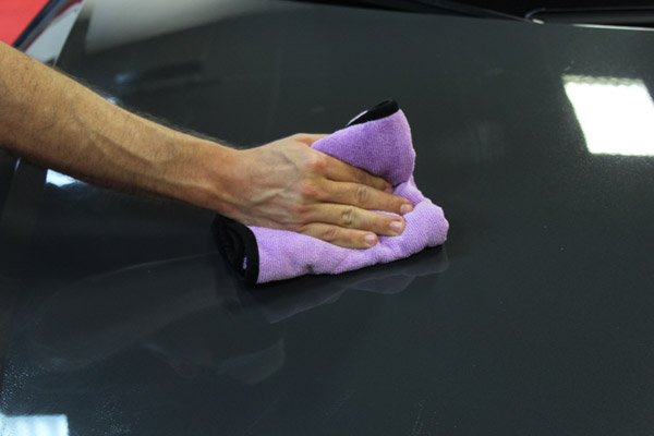 This image shows a person using a microfiber towel to wipe the excess Wolfgang PROFI Ceramic Booster off the car's paint surface.