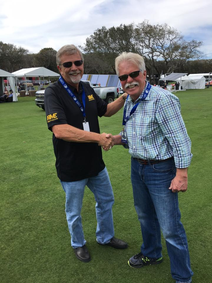 Wayne Carini and Bob McKee shake hands on the concours